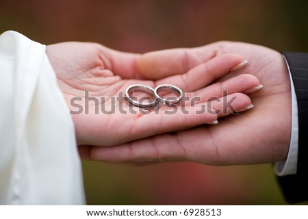 Wedding-rings in the palms of the married couple. Small DOF! - stock photo