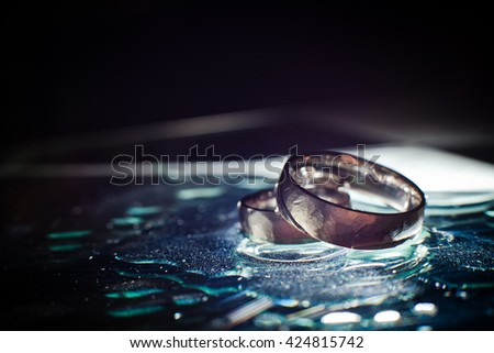 Wedding rings in water - stock photo