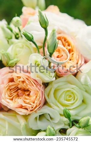 Wedding Rings Nestled in Wedding bouquet. Warm colors. Shallow dof.  - stock photo