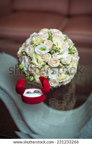 Wedding rings on a background of a bouquet of roses. - stock photo