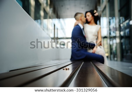 wedding rings on a background of the kissing bride and groom