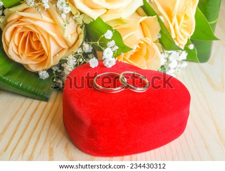 wedding rings on a heart shaped box  and  flowers - stock photo