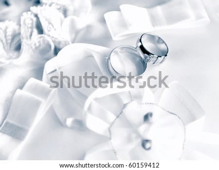 Wedding rings on a satiny fabric with bows
