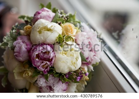 Wedding rings on a wedding bouquet. - stock photo