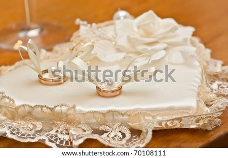 Wedding rings on a white satiny fabric - stock photo