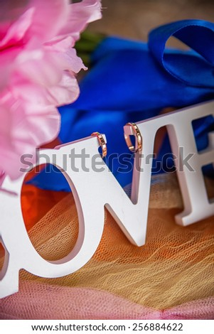 wedding rings on a wooden word Love - stock photo