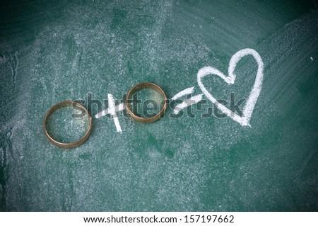 wedding rings on blackboard - stock photo