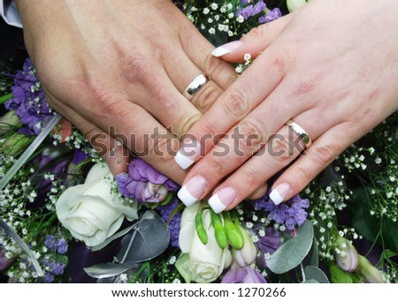 wedding rings on bride and grooms hands on top of flowers