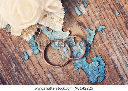Wedding rings on grunge wooden background - stock photo