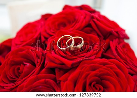 Wedding rings on red roses wedding bouquet