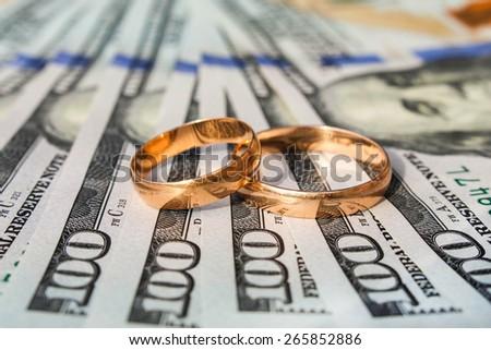 Wedding rings on the background of money hundred dollar bills  - stock photo