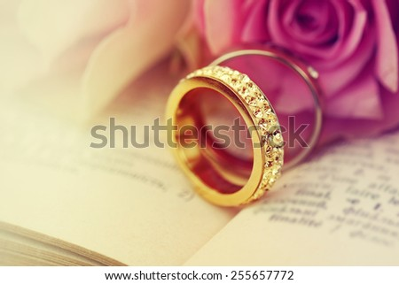 Wedding rings on the Bible. - stock photo