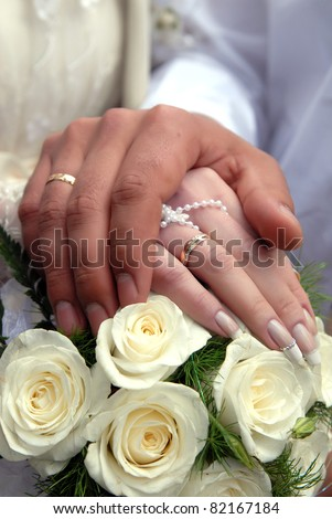 wedding rings on the groom and bride with beautiful nails and flowers - stock photo