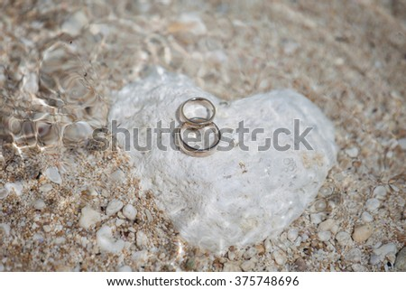 Wedding rings on the heart shaped rock under clear water - stock photo
