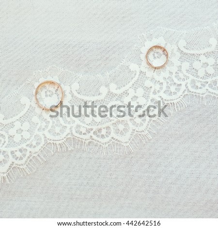 Wedding rings on the lace background - stock photo