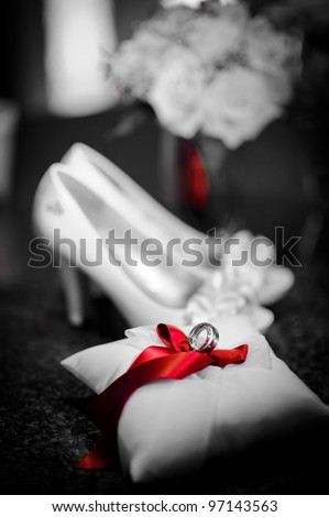 Wedding rings on the pillow and shoes - stock photo