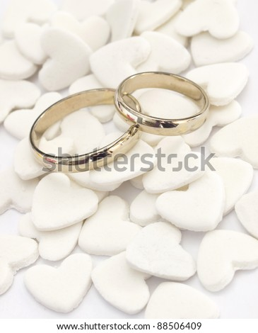 wedding rings on the white hearts background - stock photo