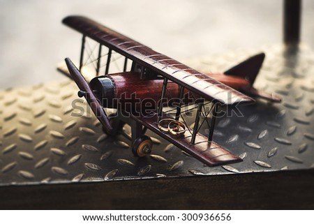 Wedding rings on the wing toy airplane - stock photo