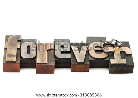 Wedding rings on the word Forever, written with vintage letterpress printing blocks isolated on white background - stock photo