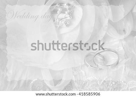 Wedding rings on wedding card, on a white wedding dress - stock photo