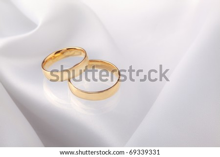 Wedding rings on white satin. - stock photo