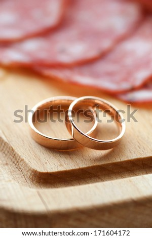 wedding rings on wooden surface with wurst - stock photo