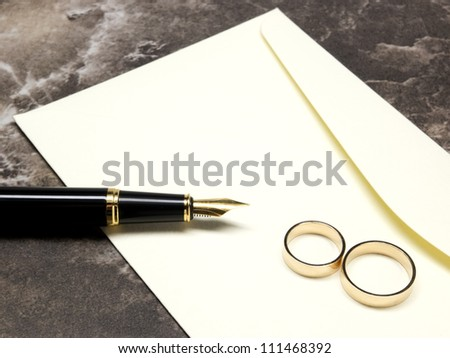 Wedding rings, pen and invitation envelope - stock photo