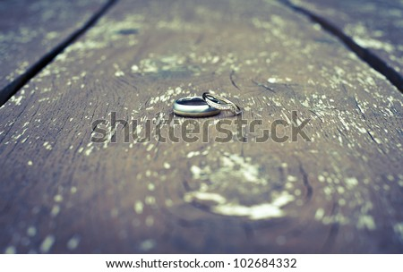 Wedding rings positioned on wooden table. - stock photo