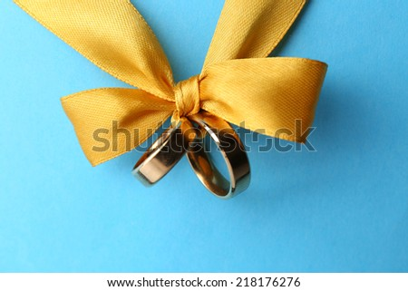 Wedding rings tied with ribbon on color background - stock photo