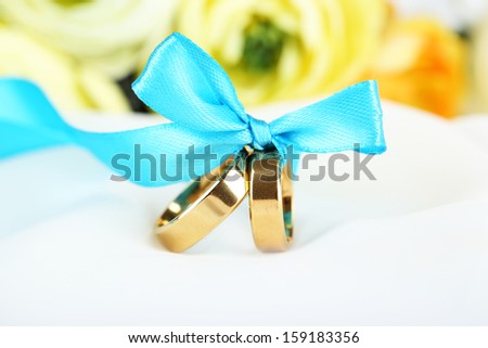 Wedding rings tied with ribbon on white fabric - stock photo
