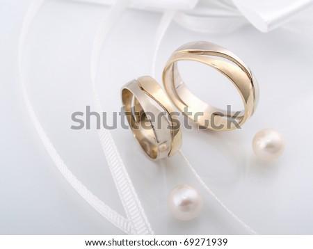Wedding rings whit white pearl. - stock photo