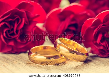 Wedding rings with red carnations on wooden background - stock photo