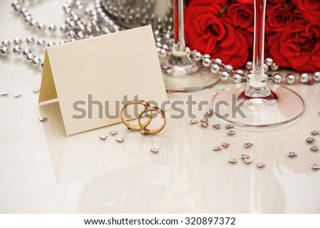 Wedding rings with writing card and champagne, copyspace - stock photo