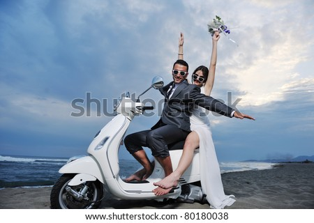 wedding sce of bride and groom just married couple on the beach ride white scooter and have fun - stock photo