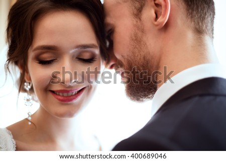 Wedding season â?? lovely young couple in a luxury interior. Handsome bearded man and lovely slim bride.