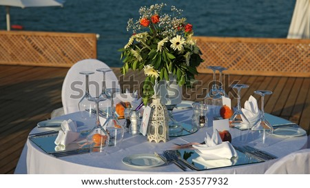 Wedding Set Up. Elegant Outdoor Wedding Table with Sea View. Wedding reception place ready for guests. - stock photo