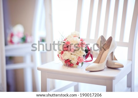 Wedding shoes and bouquet on a white chair - stock photo