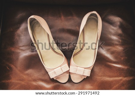 Wedding shoes beige stand on a leather sofa brown