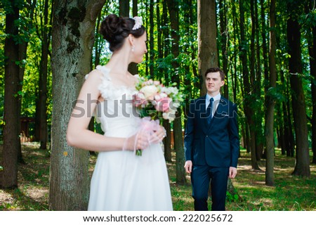 Wedding shot of bride and groom in park. summer nature outdoor. Beautiful bride and groom is enjoying his wedding day.  They kiss and hug each other - stock photo