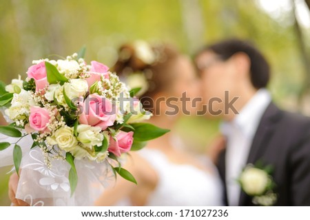 Wedding shot of bride and groom kiss in park (focus on bouquet) - stock photo