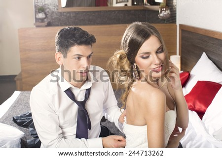 Wedding shot of bride and groom sitting on a bed  - stock photo