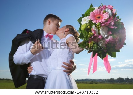 Wedding shot of bride and groom stand in field (focus on bouquet) - stock photo