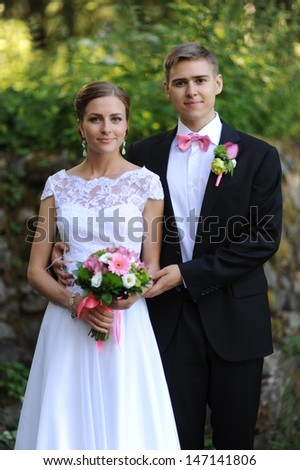 Wedding shot of bride and groom stand in park - stock photo