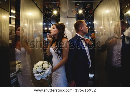 Wedding shot of couple preparing in the lift for going out