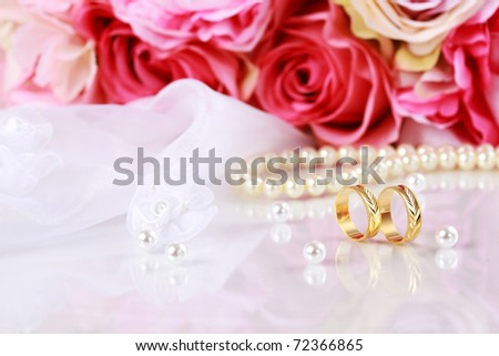 Wedding still life with beautiful golden rings and bouquet - stock photo