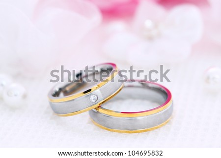 Wedding still life with beautiful golden rings and bouquet in background - stock photo