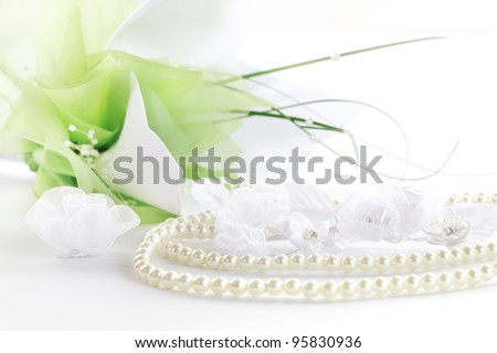 Wedding still life with necklace and bouquet in background - stock photo