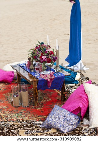Wedding table arrangement in desert sand of Morocco stile