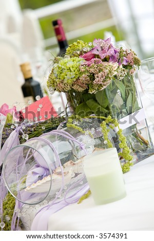 Wedding table arrangement with flowers and wine - stock photo