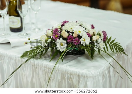 Wedding table decorated with beautiful floral bouquet. Floral compositions with fresh roses, asters and  fern leaves. - stock photo